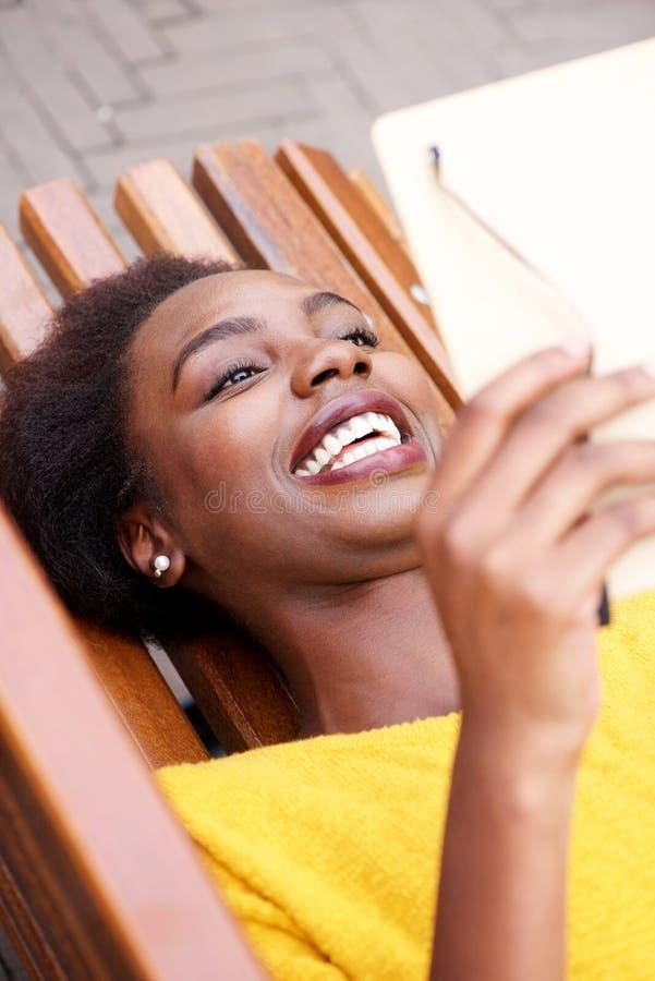 En haut du livre de lecture heureux de femme d'afro-américain photo stock