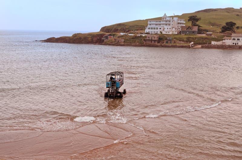 En havstraktor som korsar till Burghön i Devon, England royaltyfri bild