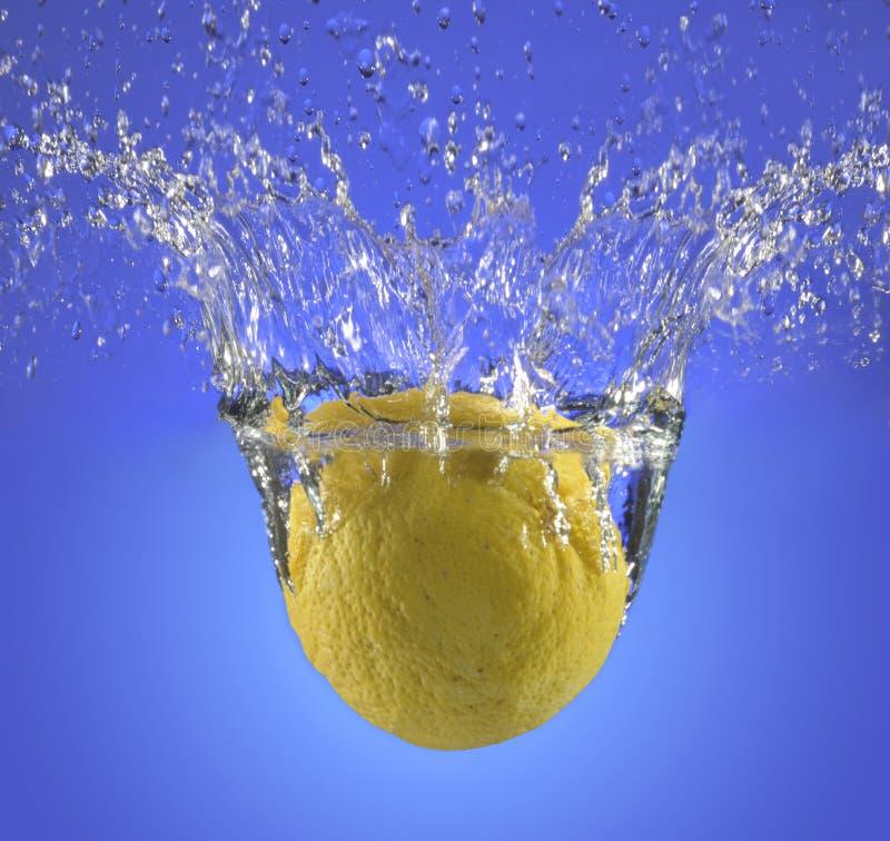 En hel citron som plaskar in i vatten arkivfoton