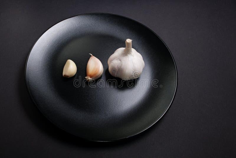En hel kula av vitlök med en enkel kryddnejlika som skalas och som är unpeeled på en svart platta royaltyfri fotografi