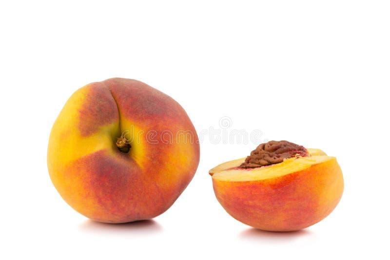 En hel persika med halva som isoleras på vit royaltyfri foto
