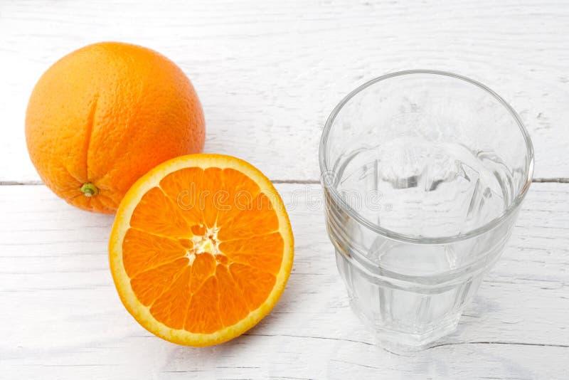 En helhet och snitthalva av apelsinen bredvid ett tomt exponeringsglas som isoleras på vitt målat trä royaltyfri bild