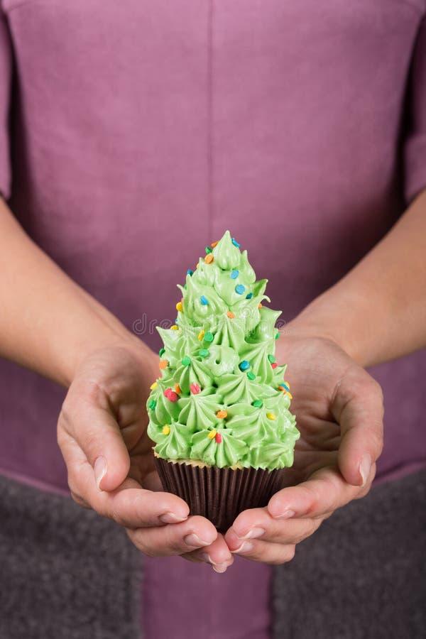 En hembra las manos son magdalenas en la forma de un árbol de navidad, concepto mínimo de la Navidad, tiro del primer fotografía de archivo libre de regalías