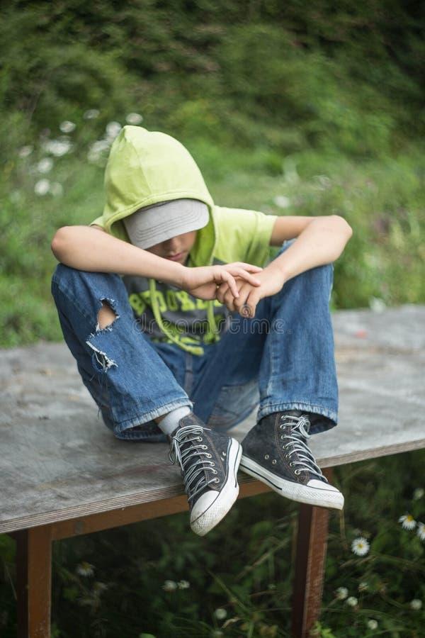 En hemlös pojke sitter på en bänk med hennes huvud som ner bugas arkivfoton