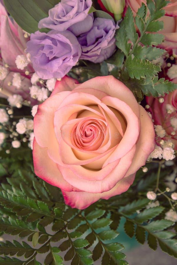 En hink av blommor med rosa färger och violetrosor arkivfoto