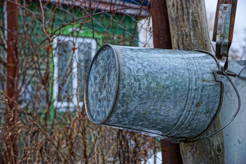 En hink för grått järn väger på en trästolpe arkivbilder