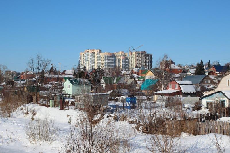 En hiver, la neige a balayé les vieilles ruines en bois de maisons de village abandonnées dans la cour sibérienne de village de c images stock