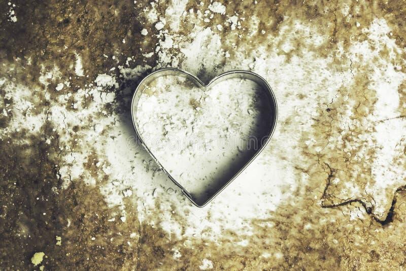 En hjärta formade bakelseskäraren på en deg med florsocker på den - arkivfoton