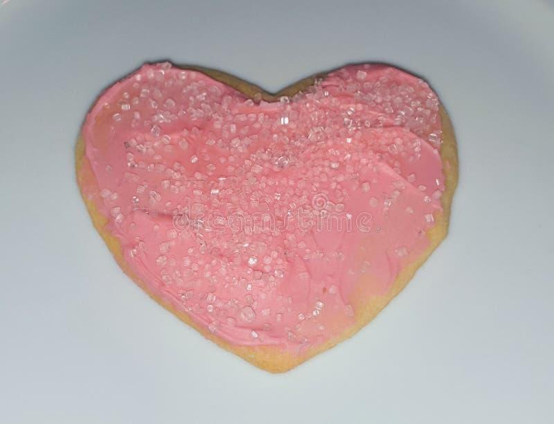 En hjärta formade sockerkakan med rosa isläggning- och rosa färgstänk för Valentine& x27; s-dag royaltyfri bild