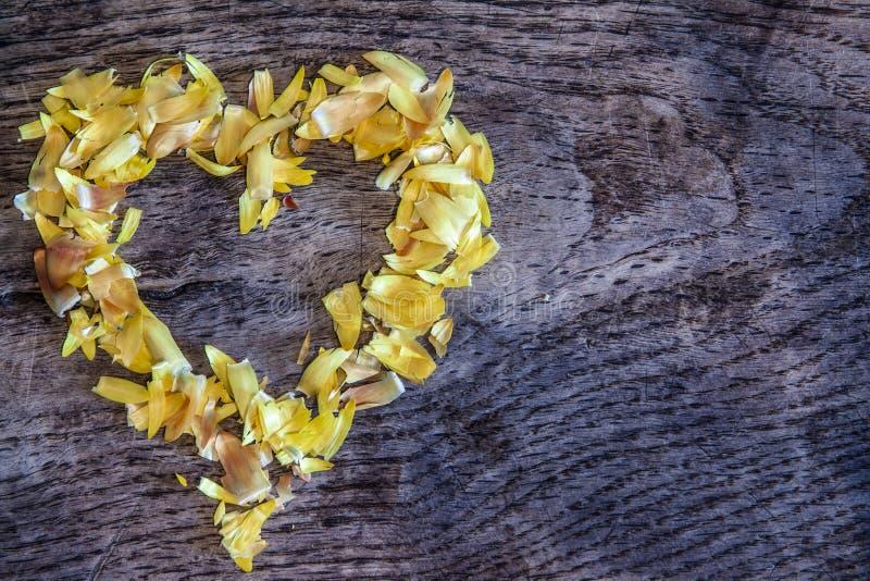 En hjärta från kronblad som ligger på en trätabell arkivfoto