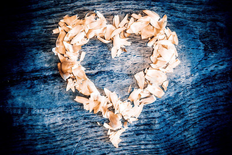 En hjärta från kronblad som ligger på en trätabell arkivbild