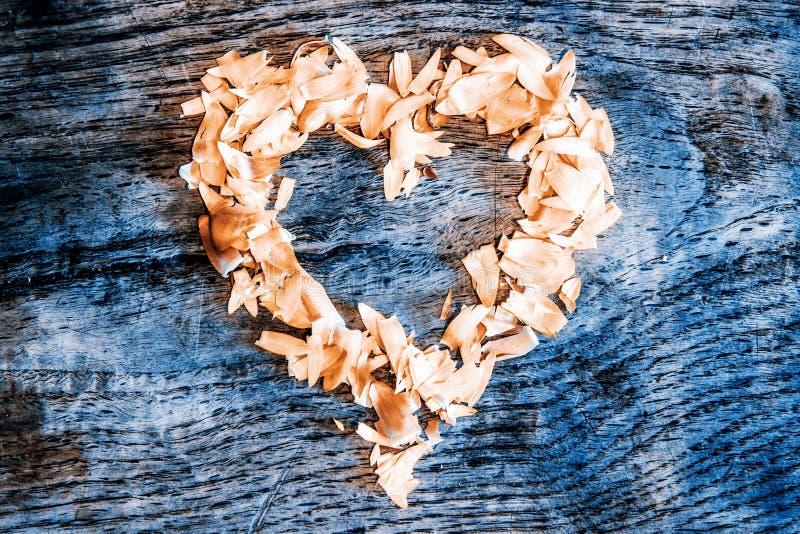 En hjärta från kronblad som ligger på en trätabell royaltyfri bild
