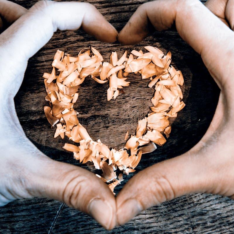 En hjärta från kronblad som ligger på en trätabell och händer royaltyfria foton