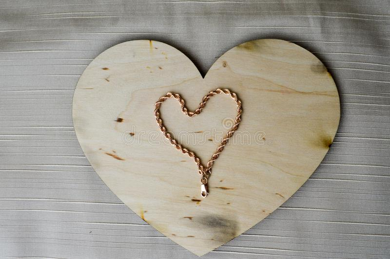 En hjärta som göras av ett kvinnligt guld- armband på ett härligt, tappning, hemlagad trähjärta till dagen för valentin` s royaltyfri foto