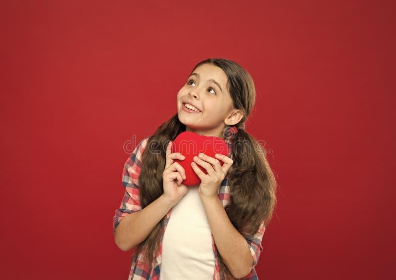 En hj?rta f?r f?r?lskelse en Liten flicka som rymmer r?d hj?rta Ha hj?rtaproblem och hj?rtesorg Litet barn som uttrycker p? f?r?l royaltyfri bild