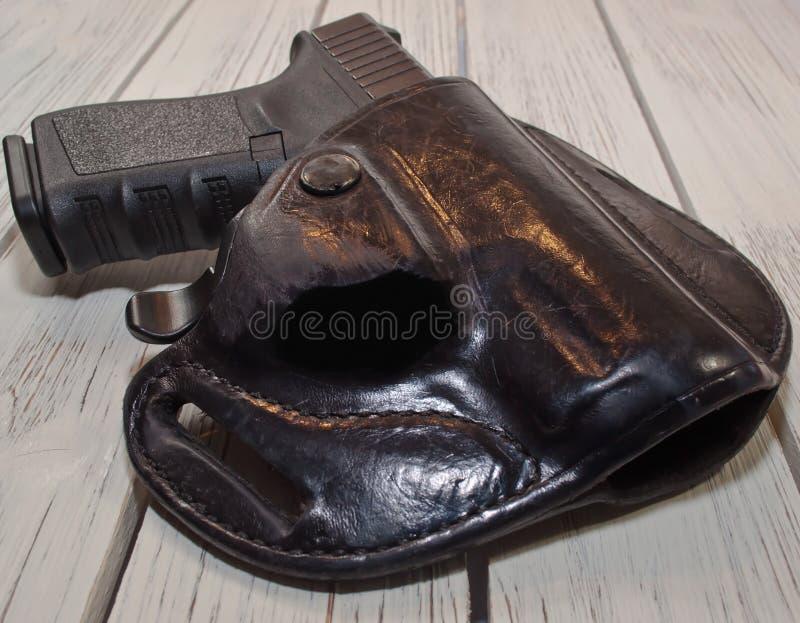 En holstered svart pistol på en trätabell fotografering för bildbyråer