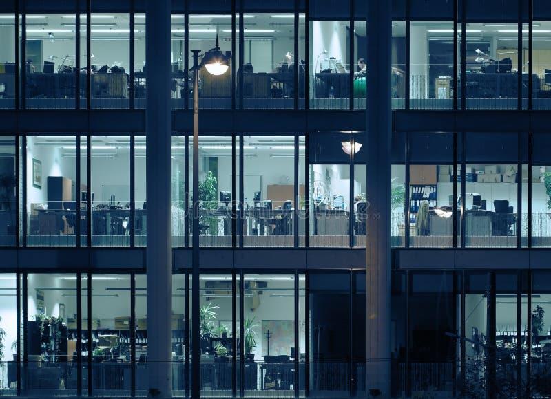 En horas extras en un edificio de oficinas moderno foto de archivo libre de regalías
