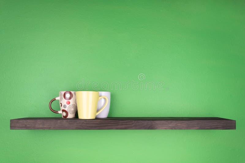En hylla för mörk färg med att texturera trä installeras på en grön vägg; på hyllan finns det tre koppar i en grupp med leavs royaltyfri bild