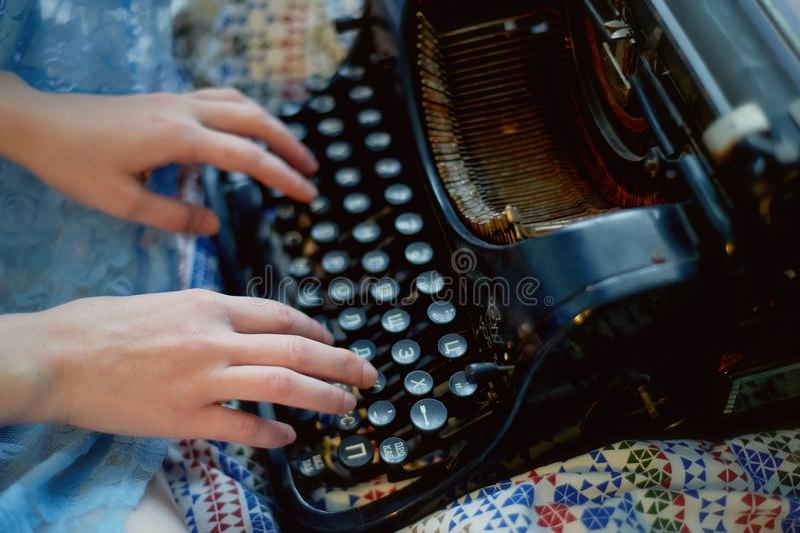 En idérik person, författare av böcker, författare av bästsäljare, en journalistmaskinskrivning på en gammal skrivmaskin Inspirat arkivbilder