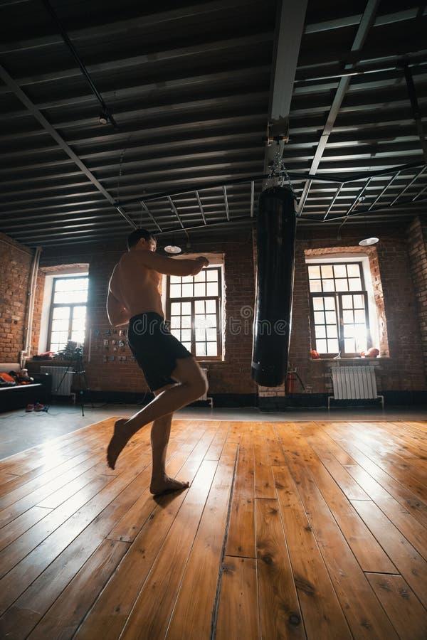 En idrotts- manboxareutbildning med en stansa påse i idrottshallen Man omkring som sparkar påsen med ett ben royaltyfri foto