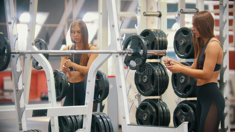 En idrottsman nenkvinnautbildning i idrottshallen - sätta en vikt på hanteln och att fästa den på plats arkivbild