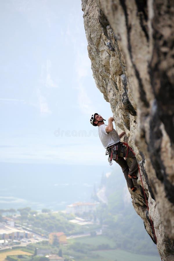 En idrottsman som klättrar på en bergvägg arkivfoton