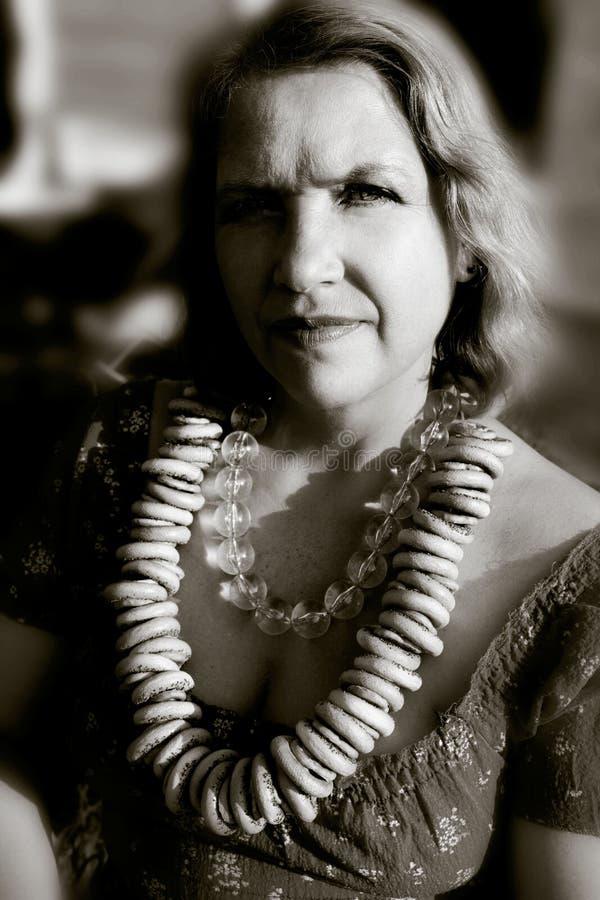 En iklädd äldre kvinna den gamla ryska stilen med en samovar, en ljus sjalett på hennes skuldror och en grupp av baglar fotografering för bildbyråer