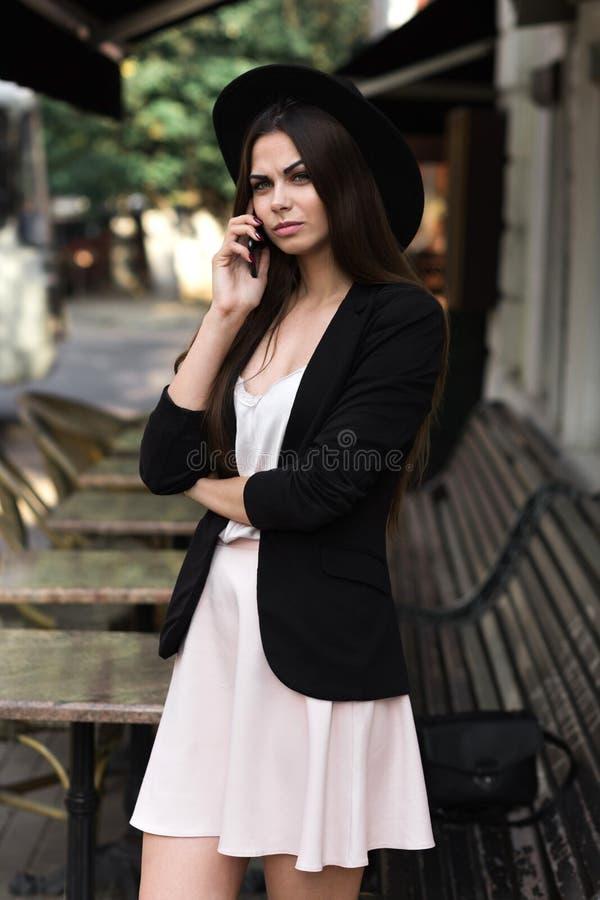 En iklädd härlig flicka en stilfull vit klänning, ett svart omslag och en svart hatt står nära marmorkaffetabellen och en w royaltyfria foton