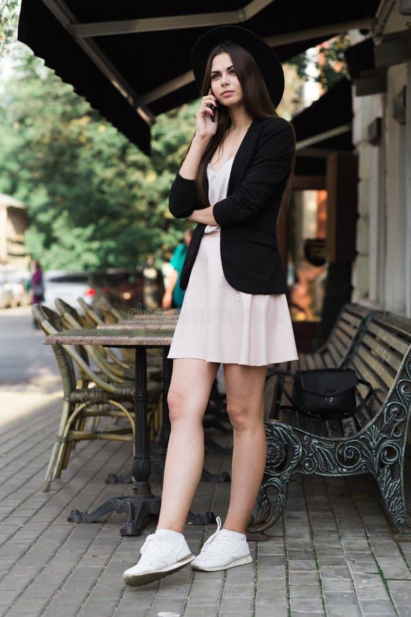 En iklädd härlig flicka en stilfull vit klänning, ett svart omslag och en svart hatt står nära marmorkaffetabellen och en w arkivbild
