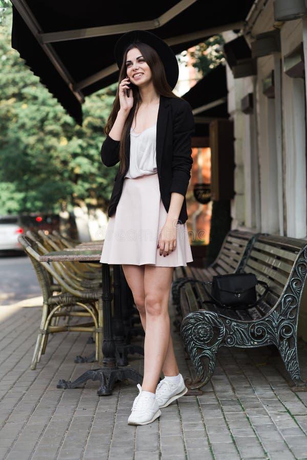 En iklädd härlig flicka en stilfull vit klänning, ett svart omslag och en svart hatt står nära marmorkaffetabellen och en w arkivbilder