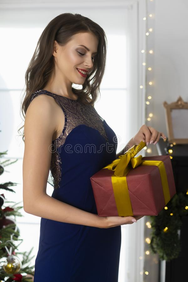 En iklädd härlig slank le flicka en lång aftonklänning packar upp en julgåva i en festlig inre Nytt år livsstil royaltyfri fotografi