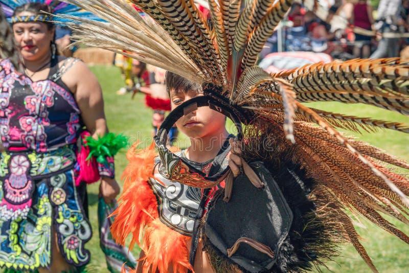 En iklädd indianregalier för ung man på powen överraskar, Malibu, CA royaltyfria bilder
