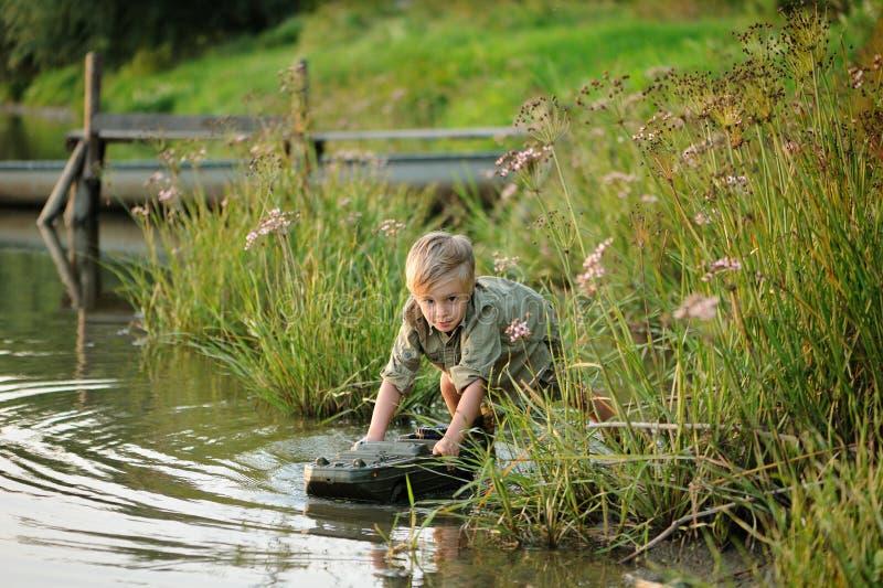 En iklädd liten ledsen pojke en militär klänning spelar vid floden royaltyfria bilder