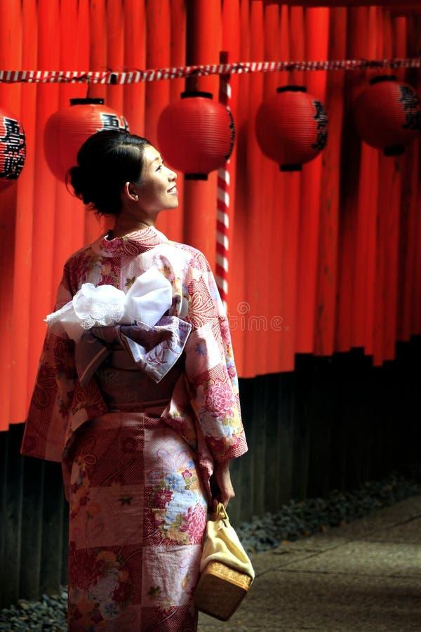 En iklädd traditionell japansk klänning för kvinna på den Fushimi-Inari relikskrin royaltyfri foto