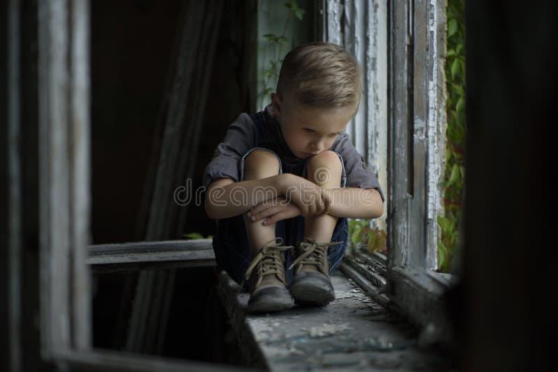 En iklädd ung ledsen pojke en retro stil, sitter han på fönsterbrädan av ett gammalt övergett hus arkivfoton