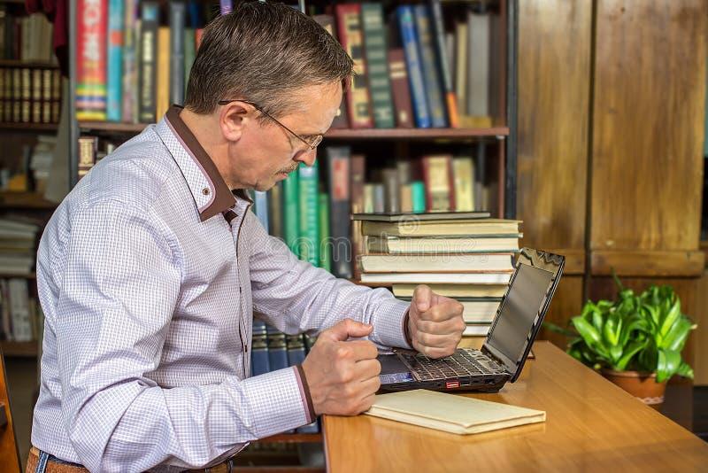 En ilsken affärsman stansar hans dator, når han har fått förargad royaltyfri foto