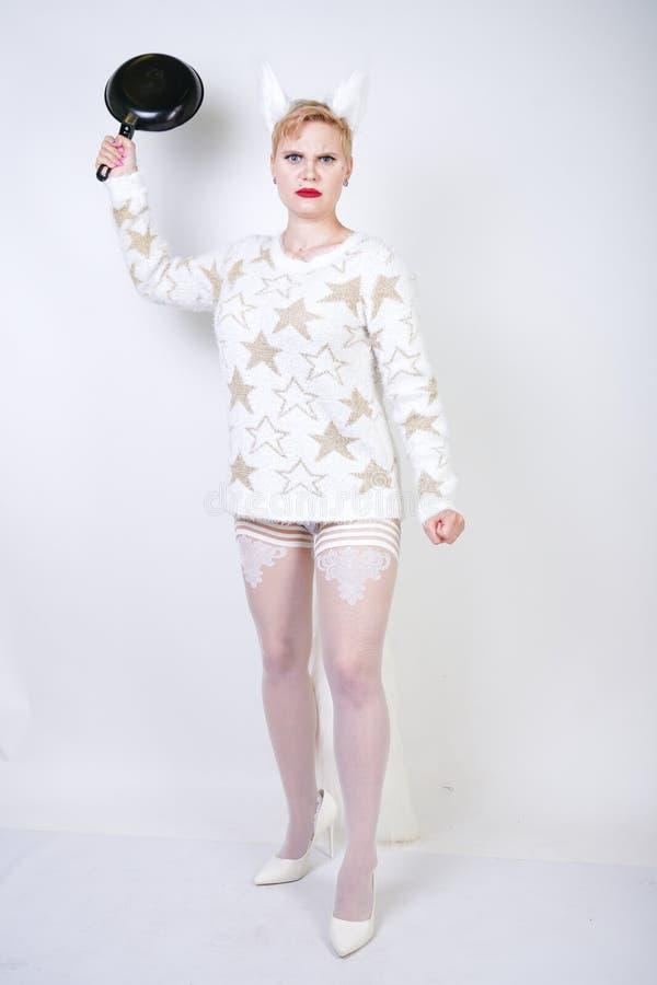 En ilsken flicka med kort blont hår i en fluffig tröja med pälsöron ont plus formatkvinna med den svarta tomma stekpannan i handn fotografering för bildbyråer