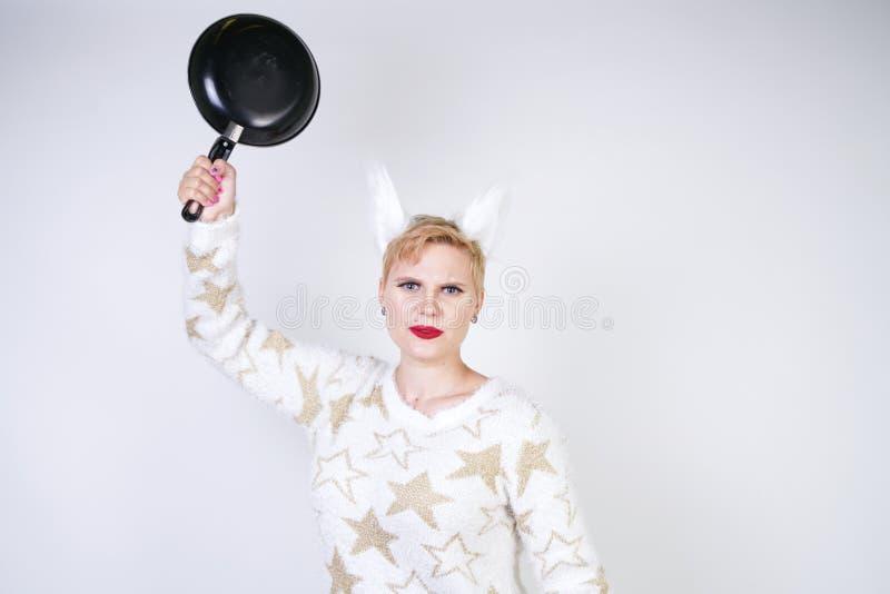 En ilsken flicka med kort blont hår i en fluffig tröja med pälsöron ont plus formatkvinna med den svarta tomma stekpannan i handn royaltyfria bilder