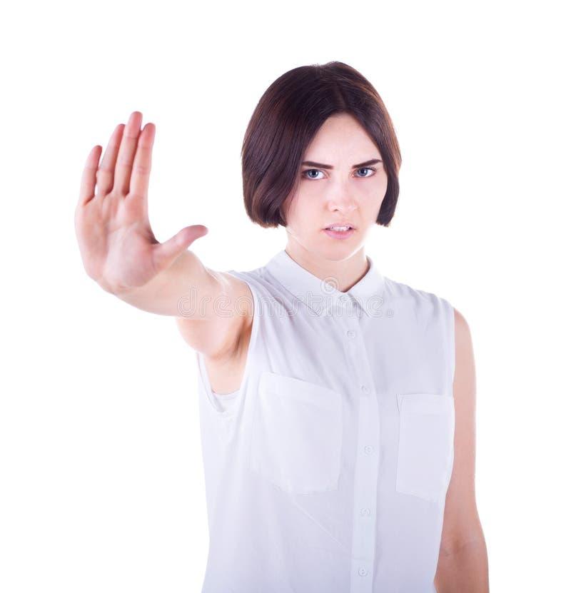 En ilsken ung kvinnlig i elegant kläder gör stopptecknet som isoleras på en vit bakgrund Protestbegrepp royaltyfria bilder