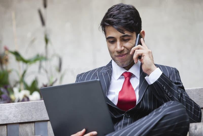 En indisk affärsman som använder minnestavlaPC, medan meddela på mobiltelefonen arkivfoton