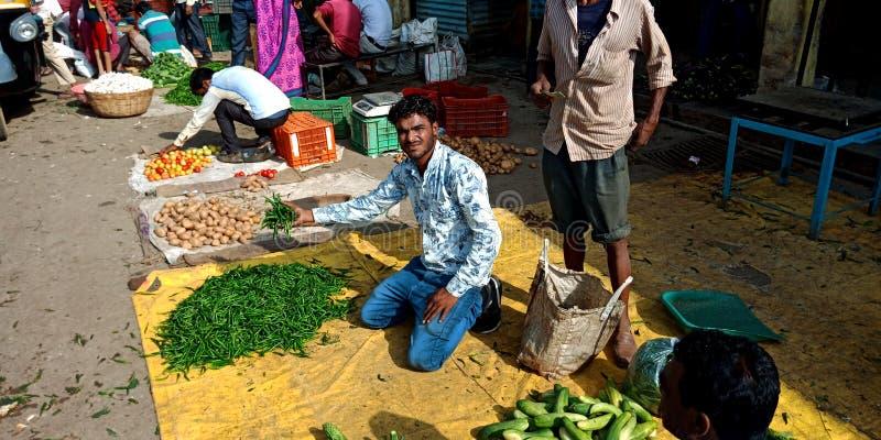 En indisk grönsakshandlare som visar nya gröna chilies till kunden arkivfoton