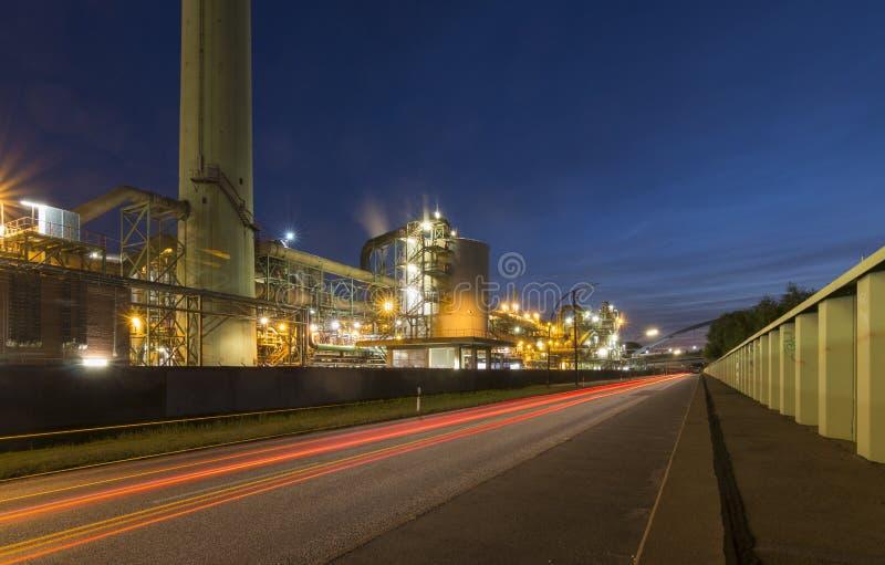 En industriell lätthet som fotograferas på natten med ljusa slingor av en bil royaltyfri fotografi