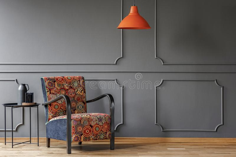En industriell sidotabell och en bohofåtölj i en elegant grå vardagsruminre med stöpningen och ställe för en coffetabell Beträffa arkivfoto