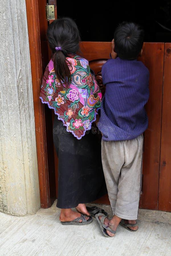 En infödd Tzotzil Mayaflicka och pojke i den traditionella klänningen som ser in i ett hus i Zinacantan, Mexico royaltyfria foton