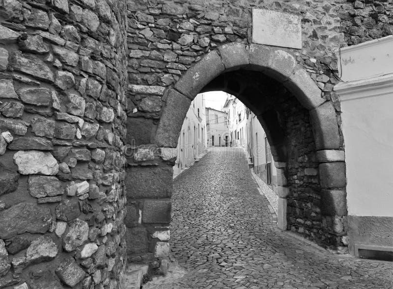 En ingång till slotten och en smal gata i svartvitt royaltyfria bilder