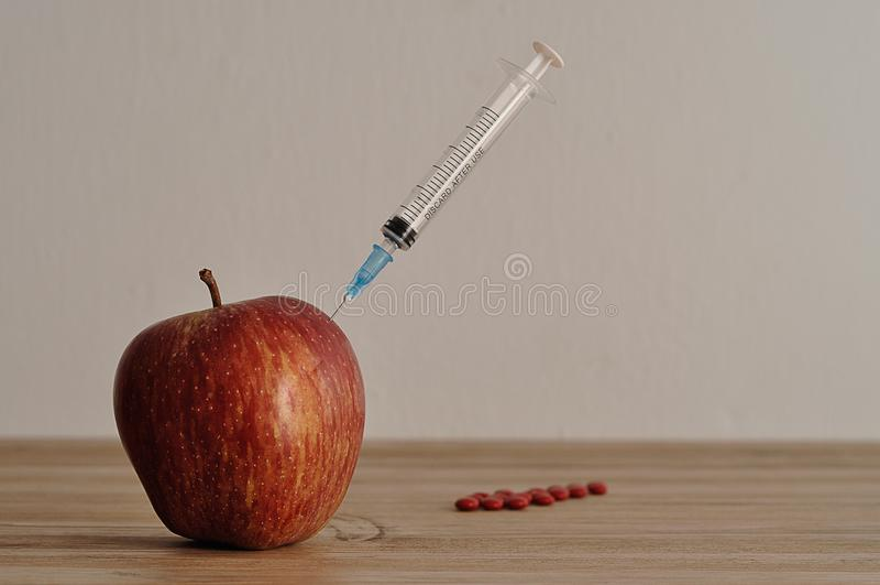En injektionvisare klibbade in i ett äpple med röda preventivpillerar royaltyfri bild