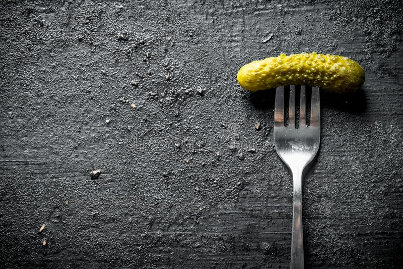 En inlagd gurka på en gaffel arkivfoton