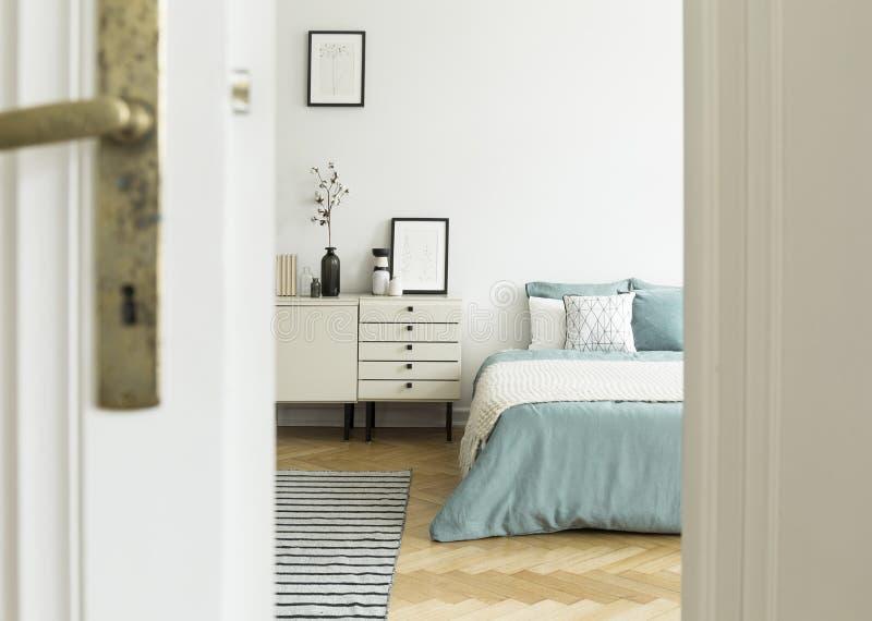 En inre för sovrum för kvinna` s med en säng och ett enhetskabinett som ses till och med en halvöppen dörr Verkligt foto royaltyfri fotografi
