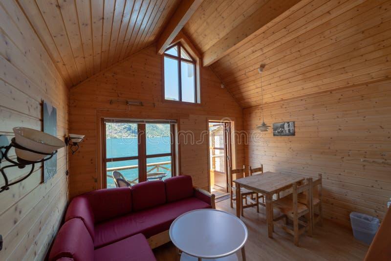 En inre sikt av ett litet semesterorthus bredvid en kustlinje, fjord, strand Bekväm slags tvåsittssoffa som ser och arkivbild