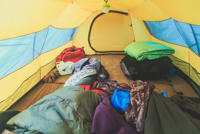 En insidasikt av tältet, processen av att campa i nedgång eller vårskogfältet som ställer in ett tält täckt arkivbilder